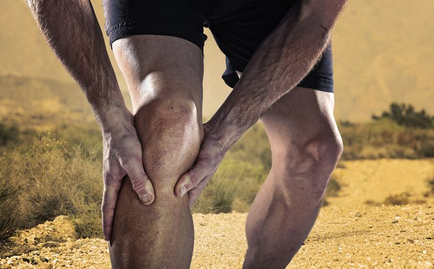 sportsman athletic legs holding knee in pain suffering muscle injury