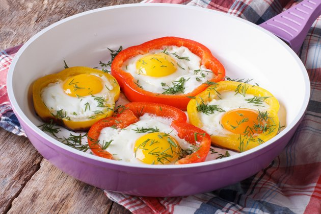 fried eggs with yellow and red peppers in pan horizontal