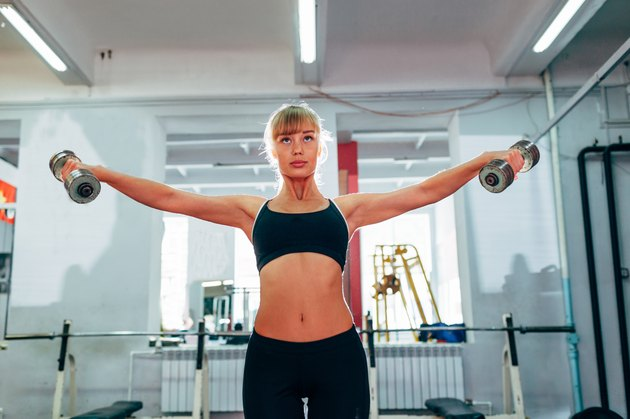 woman raising dumbbells at gym