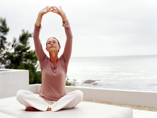 Mature woman meditating by ocean, arms raised