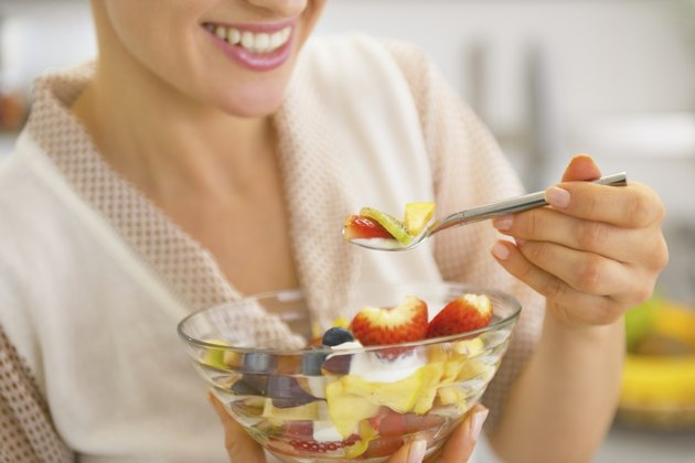 closeup on young housewife eating fresh fruit salad