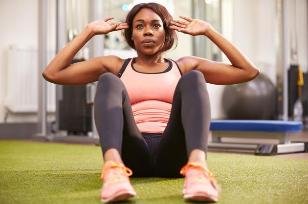Young woman doing crunches in a gym