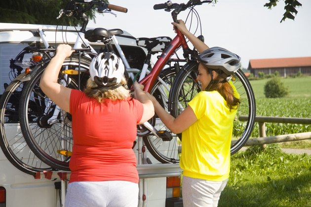 Two friends lifting bicycles from van outdoors