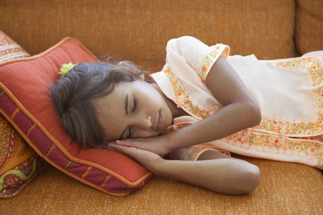 Girl (7-9) sleeping on sofa, resting head on cushion, close-up