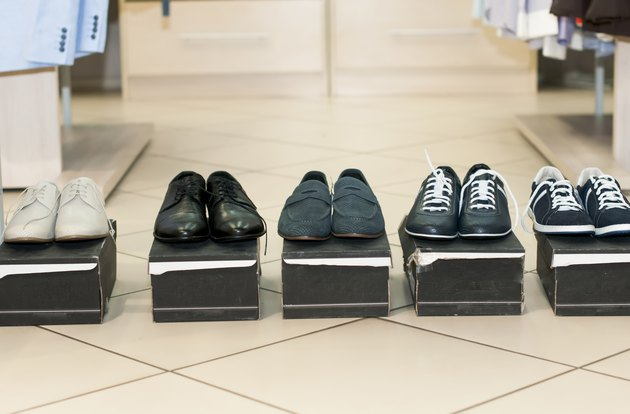 Men's shoes on black boxes.