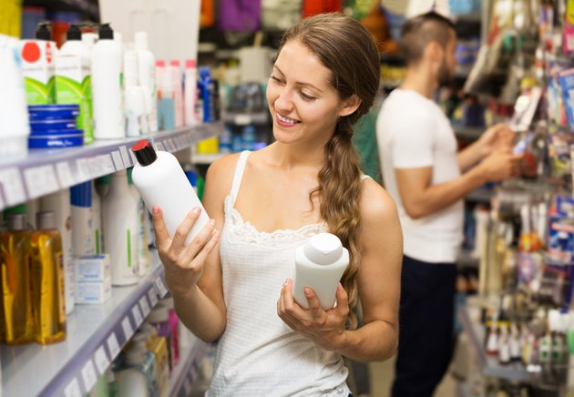 Woman selecting shampoo in store