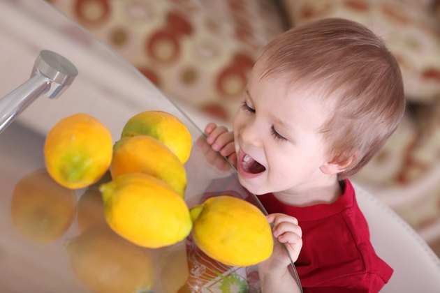 Blond hair boy eating and playing with lemons