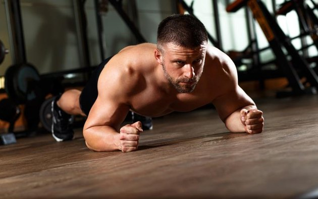 Muscular man performing plank position in gym.