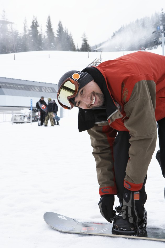Man adjusting snowboard at base of mountain, smiling, portrait