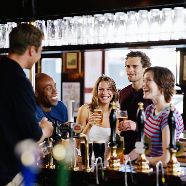 Group of friends at bar talking to barman, smiling