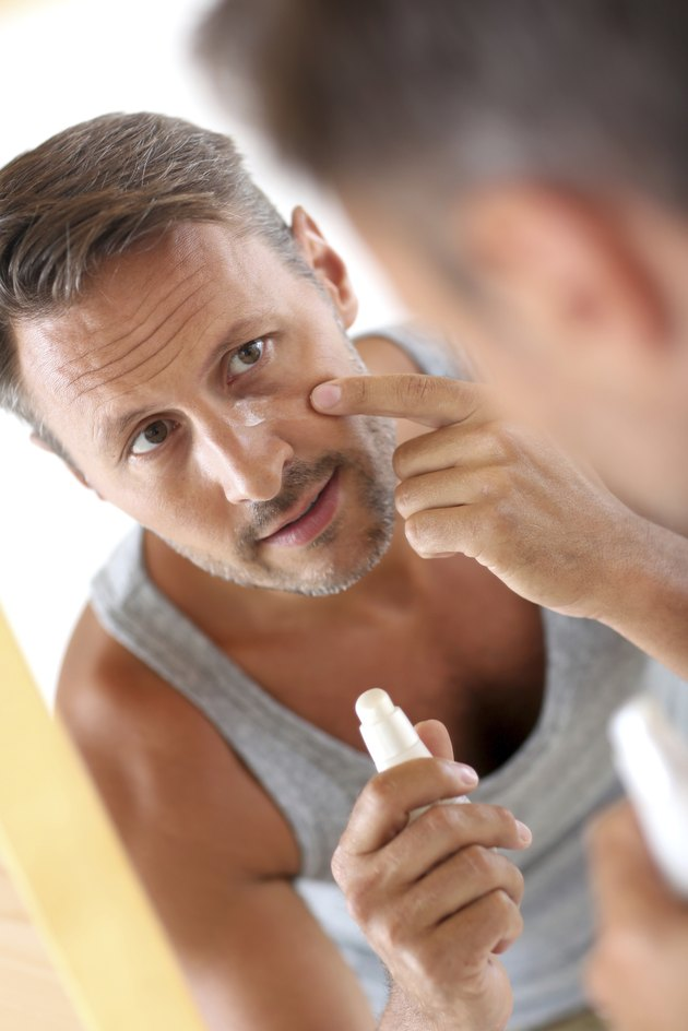 Middle-aged man applying wrinkle corrector