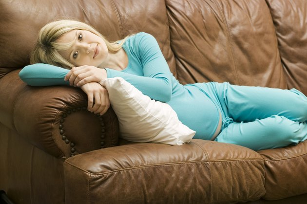 Young pregnant woman relaxing on sofa in living room, portrait