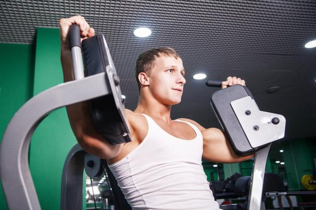 Fit young man doing machine chest presses in the gym.