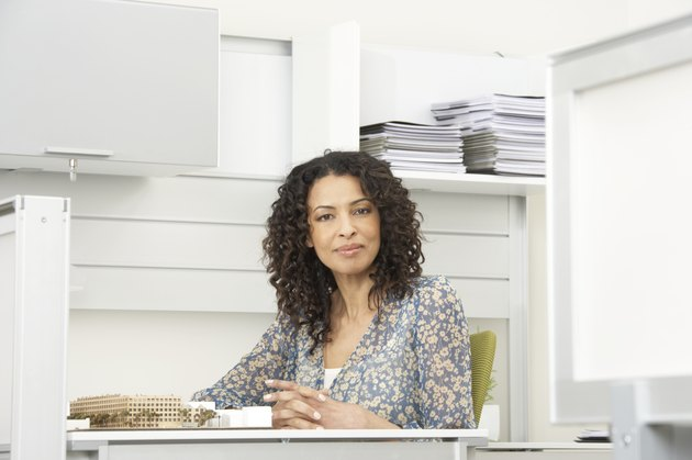 Mature businesswoman sitting at desk, smiling, portrait