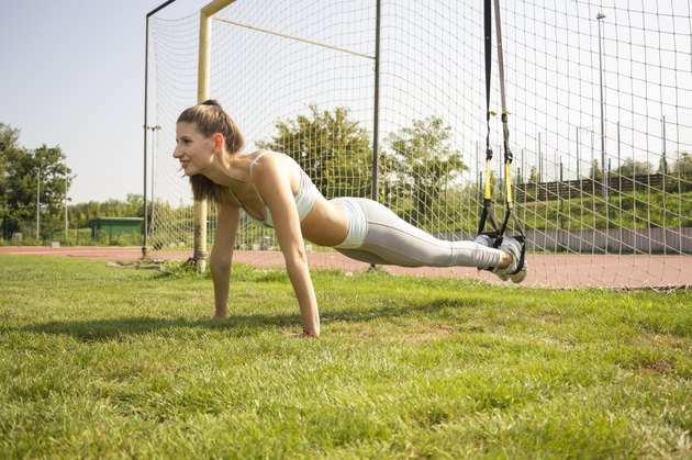 Young girl exercising outdoors on sunny day.