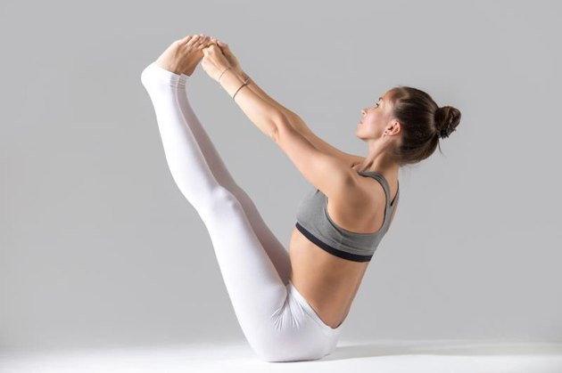 Young attractive woman practicing yoga, sitting in Both big toe exercise, Paripurna Navasana pose, working out wearing sportswear, indoor full length, isolated against grey studio background