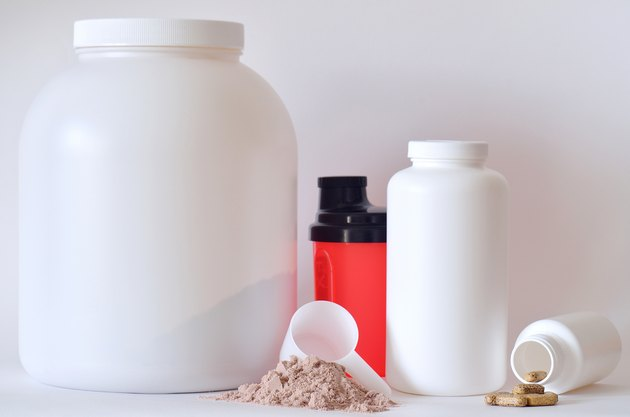 Big jar of protein powder, shaker, pills and tablets