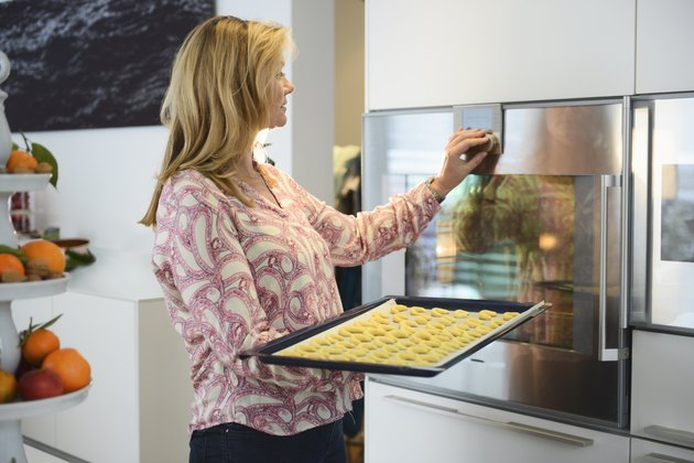 Mature woman baking cookies in kitchen