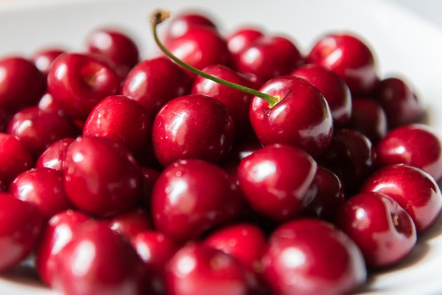 Bowl of red fresh cerries on a white background