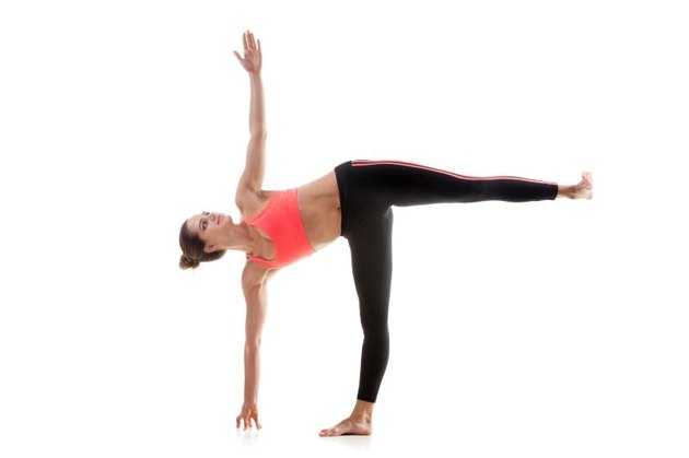 Sporty yoga girl on white background in ardha chandrasana (Half Moon Pose)