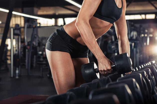 Female hands  taking dumbbells from row of barbells in a gym