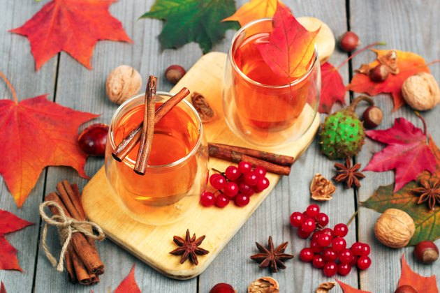 Autumn hot beverage in a glass with fruits and spices