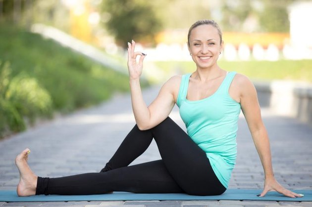 Sporty smiling attractive young woman practicing yoga, sitting in Half lord of the fishes exercise, Ardha Matsyendrasana pose, working out, outdoor full length, street background, looking at camera