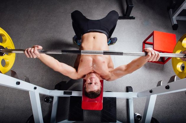 young bodybuilder training in the gym: chest - barbell incline bench press - wide grip, top view