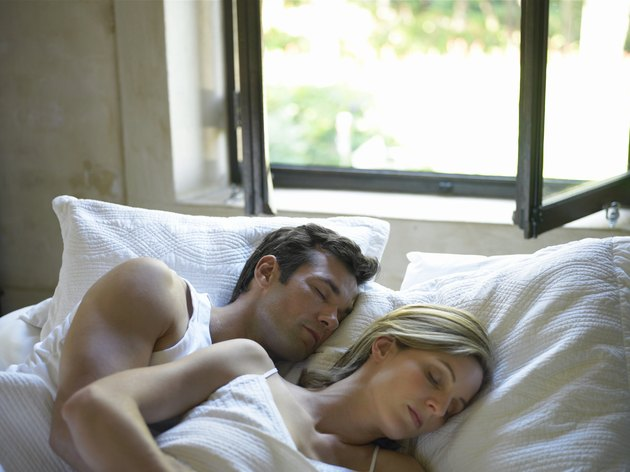 Couple sleeping in bed under open window