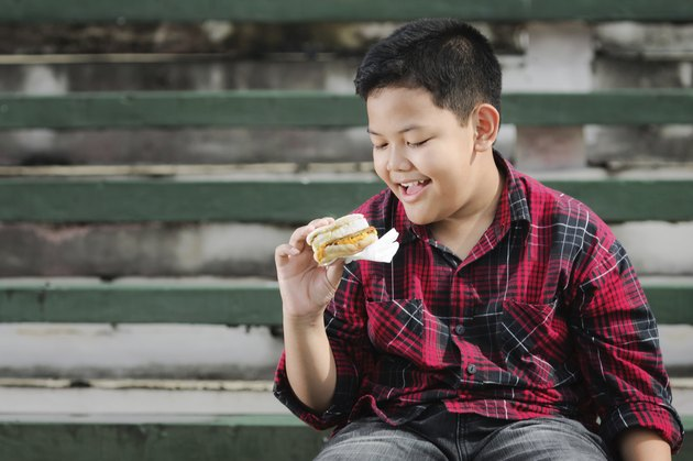 asian boy holding a sandwich