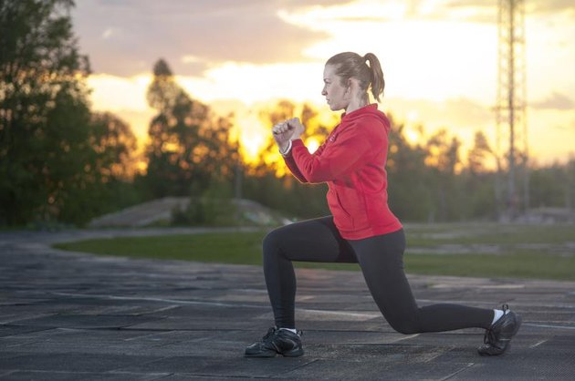 Young fit woman doing squats (frontal lunges) outdoors. Fitness, workout, sport outdoors concept.