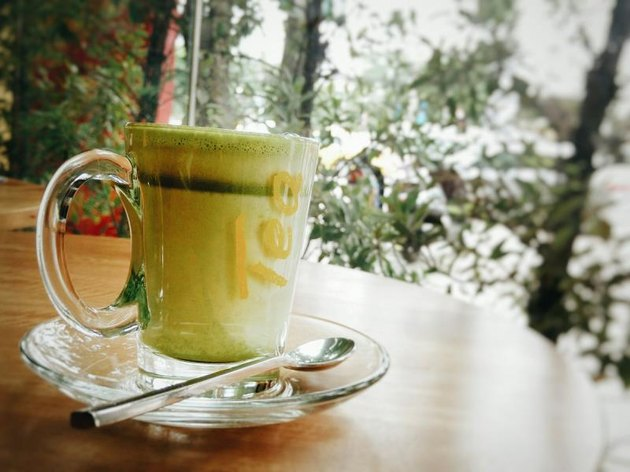 Cup Of Green Tea Latte On Table