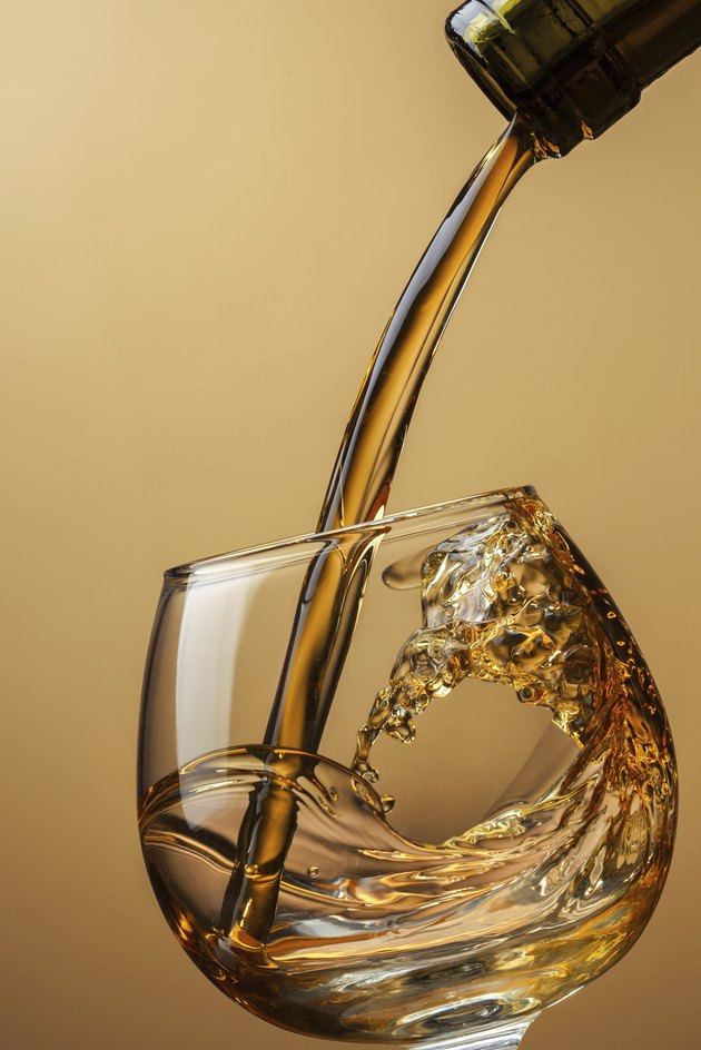 Cognac pouring from bottle into glass with splash on brown