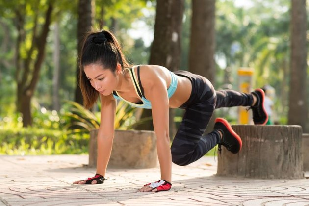 young woman doing plank exercise outdoors