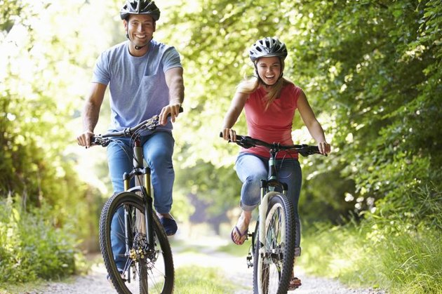 Couple On Cycle Ride In Countryside Smiling At Camera