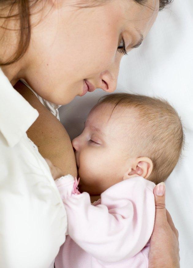 happy mother breast feeding her baby girl
