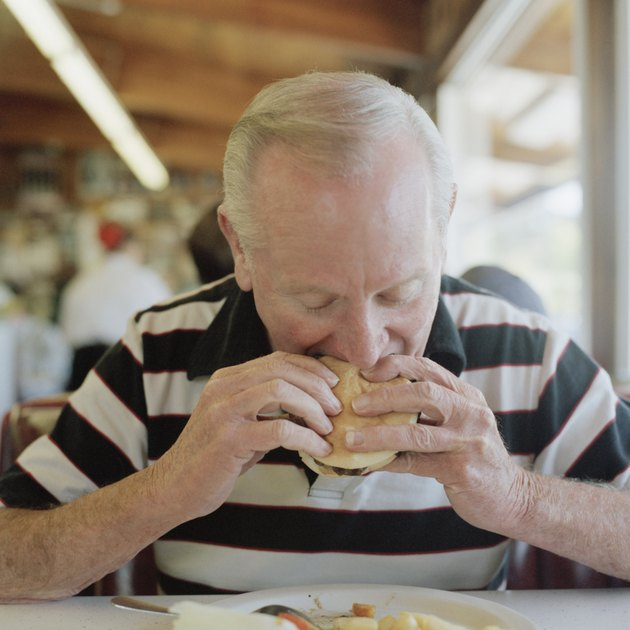 A senior man eating a hamburger