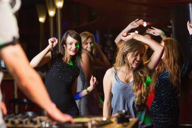 Happy friends dancing by the dj booth