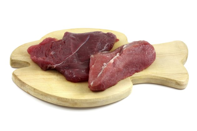 Fresh Ostrich meat on a wooden board