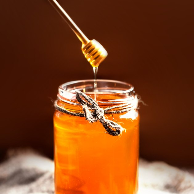 Fresh Honey in jar with  dipper on vintage wooden