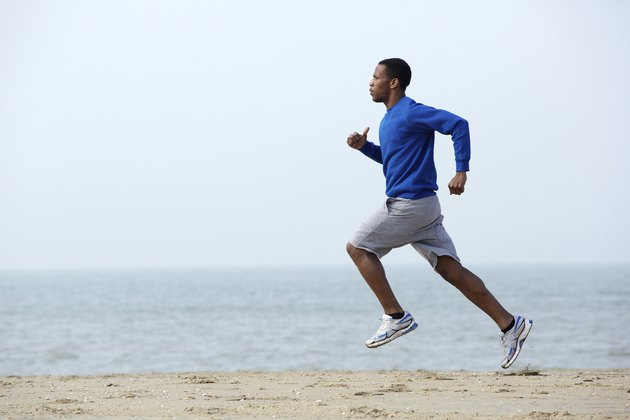 Young athletic man running at the beach