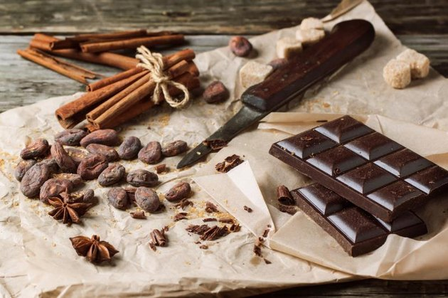 Dark chocolate with knife,  cocoa beans, cinnamon and anise on crumpled paper over wooden background