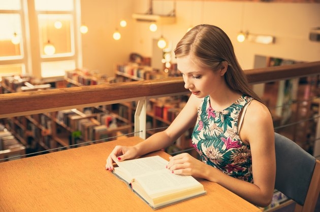 Beautiful young woman student in library reading a book