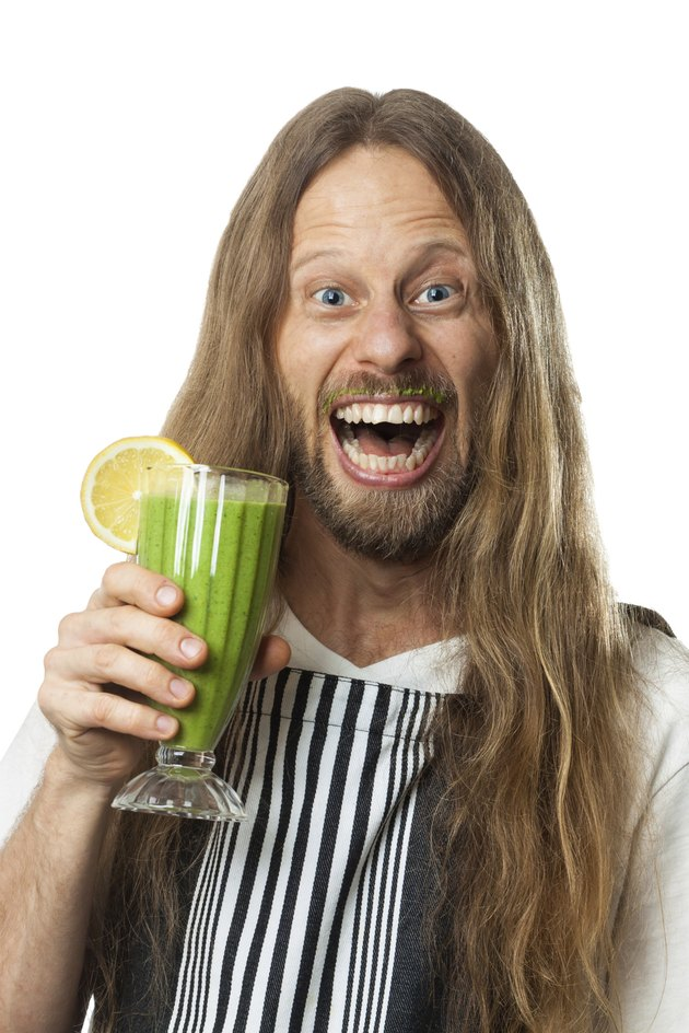Happy hippie drinking green vegetable smoothie on white