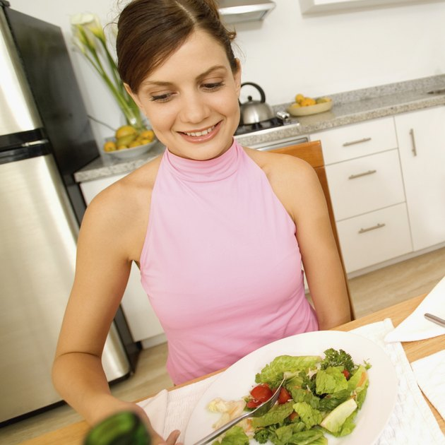 Young woman eating salad in kitchen, close-up, tilt