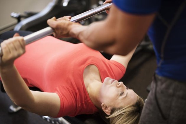 A woman at the gym prepares to bench press as her trainer spots her.