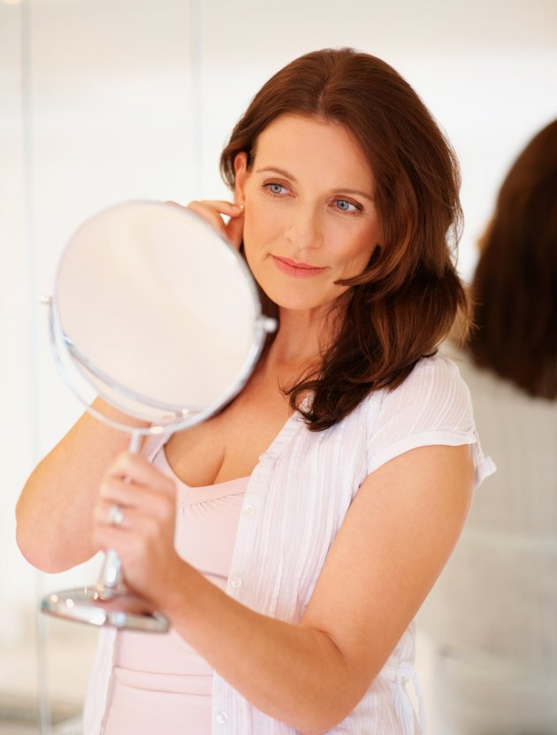 Happy mature female looking into mirror