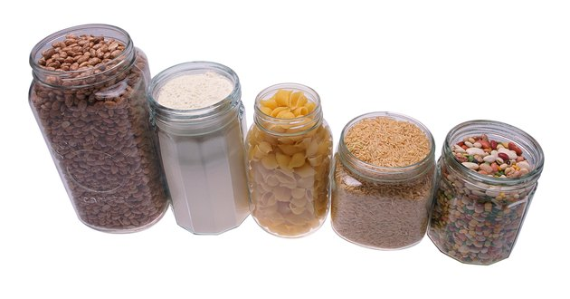 Jars in row, filled with beans, grain, breakfast cereal, and flour
