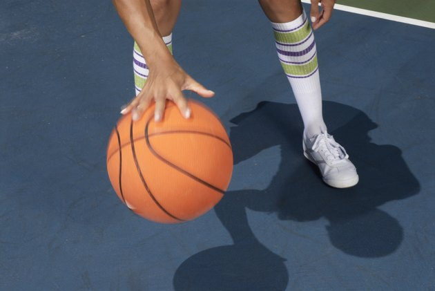 Woman standing dribbling basketball, low section, blurred motion