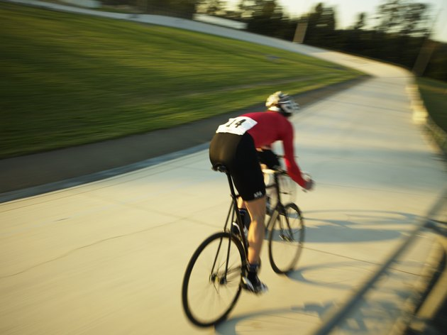 Cyclist on velodrome track, rear view